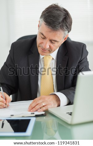 Business man writing on a notepad on his table in his office - stock photo