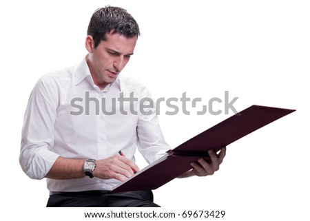 Business man writing on financial book - stock photo