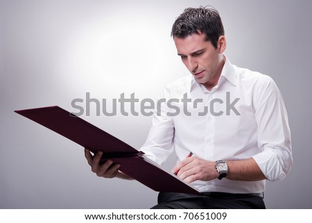 Business man writing on financial book