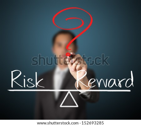 business man writing question with risk compare to reward on balance bar - stock photo