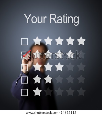 business man writing red mark on four star choice on rating survey form - stock photo
