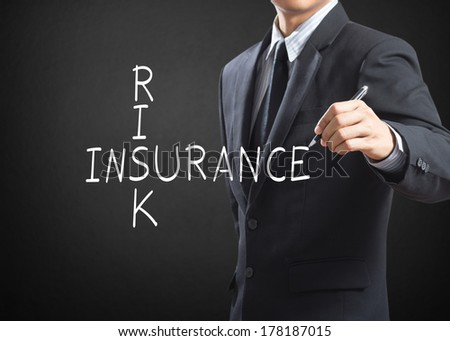Business man writing Risk Insurance crossword - stock photo