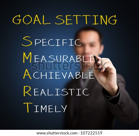 business man writing smart goal or objective setting - specific - measurable - achievable realistic - timely - stock photo