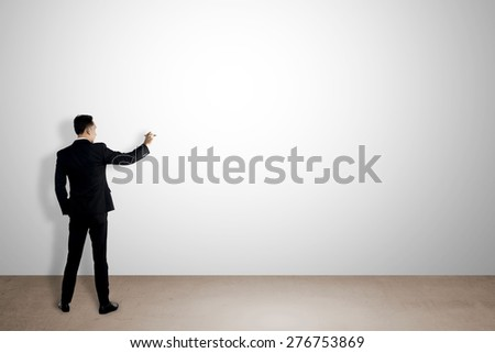 Business man writing something on empty white wall. You can put your message on the wall - stock photo