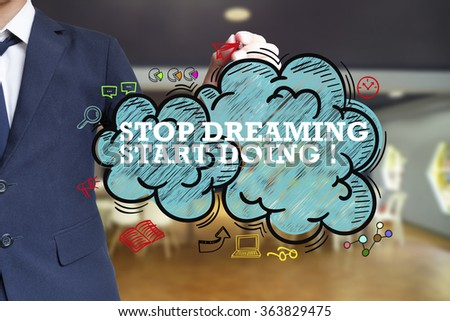 business man writing STOP DREAMING START DOING over the cloud with office background , business concept , business idea - stock photo