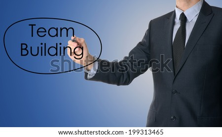 business man writing team building concept on blue background - stock photo