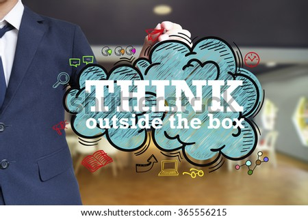 business man writing THINK OUTSIDE THE BOX over the cloud with office background , business concept - stock photo