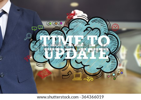 business man writing TIME TO UPDATE over the cloud with office background , business concept , business idea - stock photo