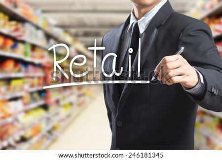 Business man writing word retail in the supermarket - stock photo