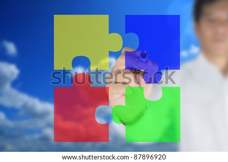 business man written puzzle pieces on the transparent board - stock photo