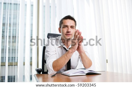 Business manager clasped his hands in front of him while sitting at the table in board room. Handsome man in business suit posing for the camera. - stock photo