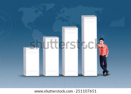 Business manager is standing next to bar chart on blue background - stock photo