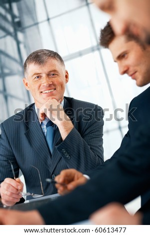 Business manager smiling and holding his glasses working with his team.
