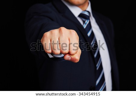 Business manager with clenched fist on dark background