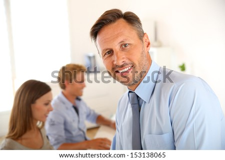 Business manager with employees in background - stock photo