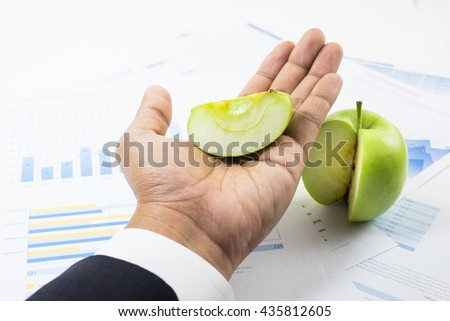 Business market share and success concept.A piece of green apple on businessman hand. - stock photo