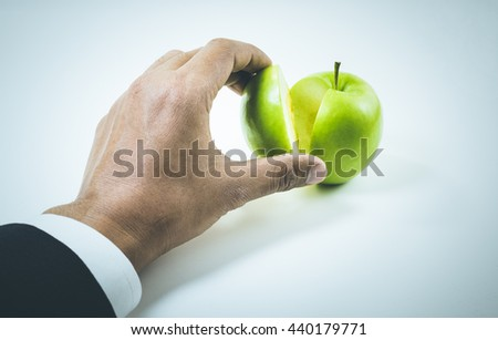 Business market share and success concept.Businessman hand pick a piece of green apple up . - stock photo