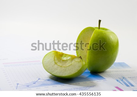 Business market share and success concept.Green apple slice on paper graph. - stock photo