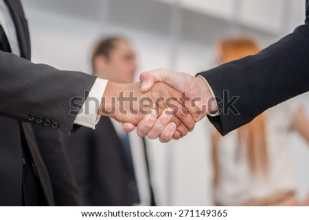 Business meeting and shaking hands. Two successful businessman standing at the table looking at each other shaking hands - stock photo