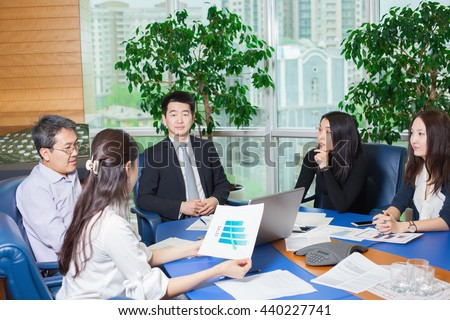 Business meeting, Asian people sitting for table with business plan on high floor in the office. Asian nationality male and woman. woman keeping a business chart in his hand - stock photo