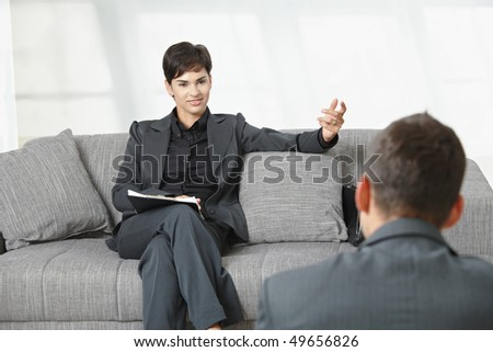 Business meeting at office. Businesswoman sitting on sofa having job interview, smiling. - stock photo