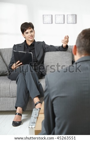 Business meeting at office. Female consultant sitting on sofa talking to partner, smiling.