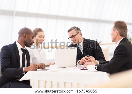 Business meeting. Business people in formalwear discussing something while sitting together at the table - stock photo