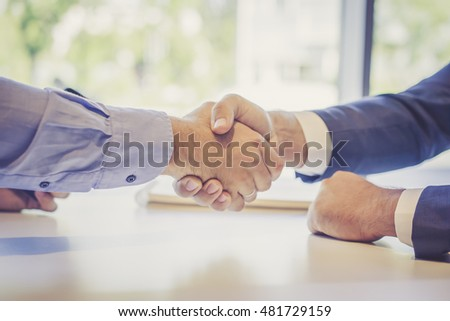 Business meeting, close-up of male handshake, men sits next to the window at a white table in front of each other, selective focus, film effect, blurred background.