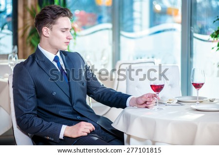 Business meeting. Confident businessman in formal wear sitting at a table in a restaurant while holding a glass of wine and looking away - stock photo