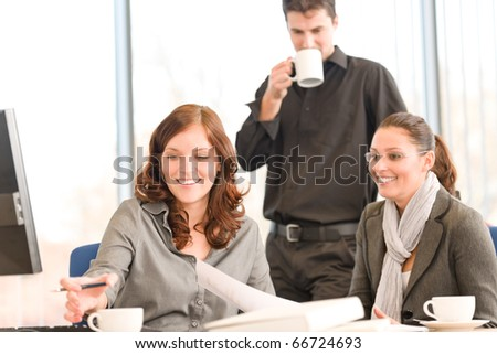 Business meeting - group of people in office sitting at computer desk - stock photo