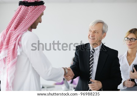 Business meeting - Handsome young Arabic  man presenting his ideas to colleagues and listening for ideas for success investments at bright modern office room - stock photo