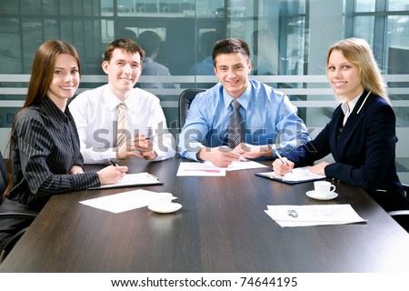 Business meeting - Happy businesspeople look at camera - stock photo