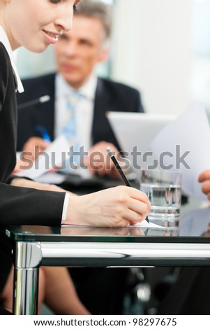 Business - meeting in an office, lawyers or attorneys discussing a document or contract agreement - stock photo