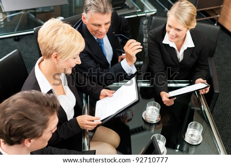 Business - meeting in an office; the businesspeople are discussing a project