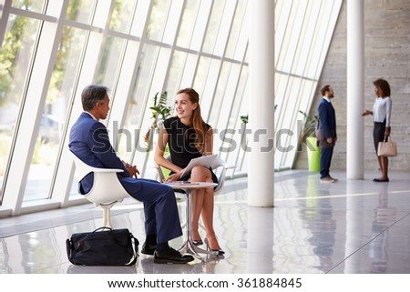 Business Meeting In Busy Office Foyer Area - stock photo