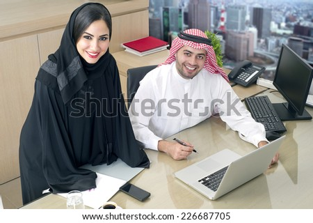Business Meeting in office , arabian businessman & arabian Secretary wearing hijab working on laptop - stock photo