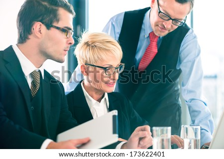 Business - meeting in office, businesspeople are discussing documents on Laptop and tablet computer - stock photo