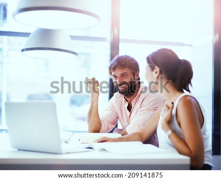 Business meeting in office, businesspeople working with laptop, couple of beautiful colleagues smiling having a work, two partners having good idea smiling together, teamwork with businesspeople - stock photo