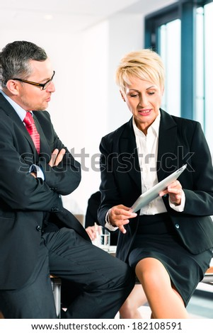 Business - meeting in office, two senior managers are discussing a document on tablet computer - stock photo