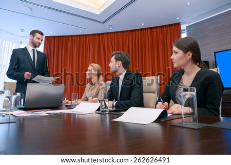Business meeting in progress. Low angle view on group of managers at business meeting in formalwear looking at their leader ready to discuss business analytics and put down information to their - stock photo