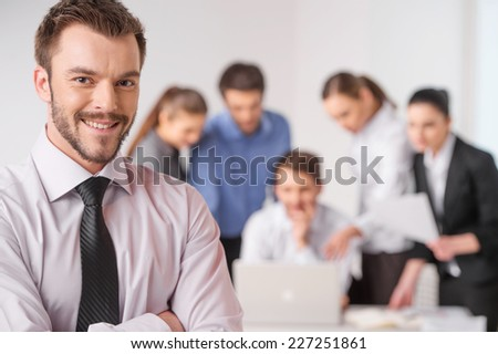 Business meeting - manager discussing work with his colleagues. closeup on man standing on foreground with crossed hands and team on background - stock photo