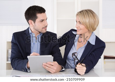 Business meeting: professional successful team; managing director and assistant with tablet computer at the office. Also flirting at workplace situation. - stock photo