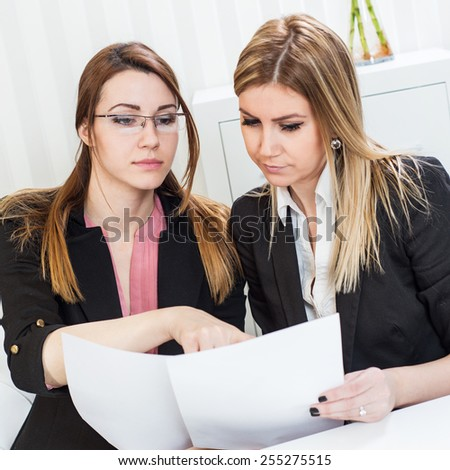 Business meeting, showing contract document, casual conversation at office, two beautiful females. - stock photo