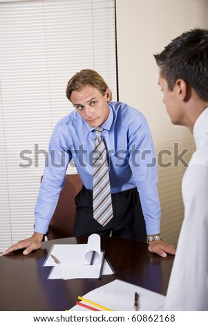Business meeting - skeptical office worker looking at colleague in boardroom - stock photo