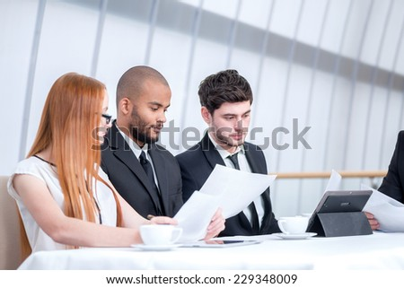 Business meeting. Three confident successful businessmen at a meeting while sitting at a table discussing business affairs in the office on laptop