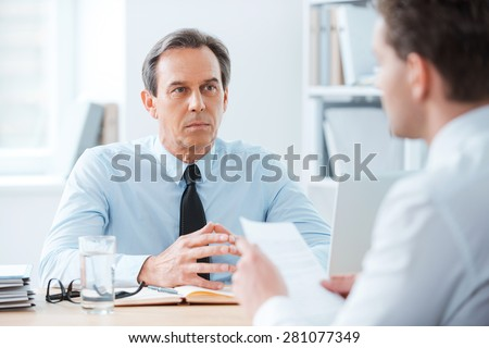 Business meeting. Two business people sitting in front of each other in the office while discussing something - stock photo