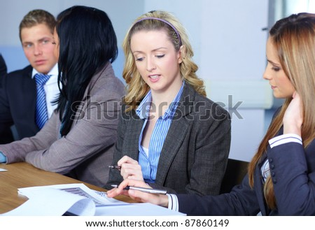 Business meeting, two females on the foreground work on some paperwork, while two other colleagues discuss something in the background, all sitting at conference table. - stock photo