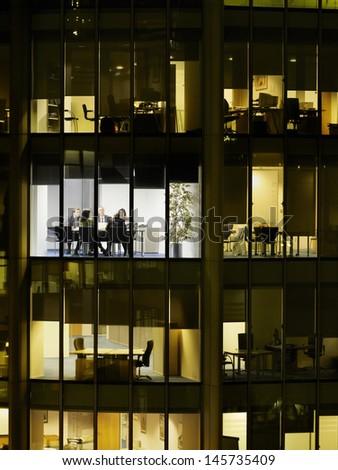 Business meeting viewed through illuminated window of office block at night - stock photo
