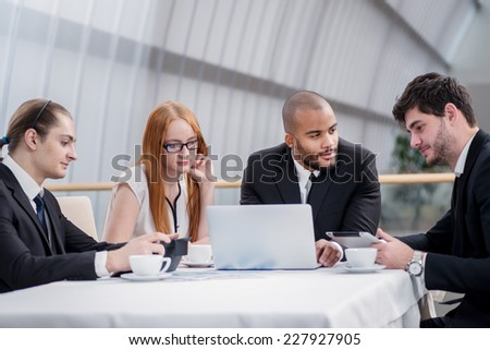 Business meeting with colleagues. Four smiling successful businessmen sitting at table in office while discussing their business doings. Young men dressed in formal wear - stock photo