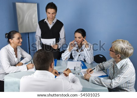 Business meeting with group of people,a businessman making a speech and reading from a paperwork and a businesswoman drinking water and thinking while the others having a conversation - stock photo